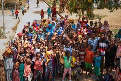 Residents-of-Millennium-Camp---a-camp-for-internally-displaced-people---in-Dire-Dawa,-Ethiopia-waving_66A5517