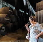 Woman tasting wine, with wine barrels in the background