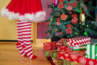 Child decorating Christmas tree with presents
