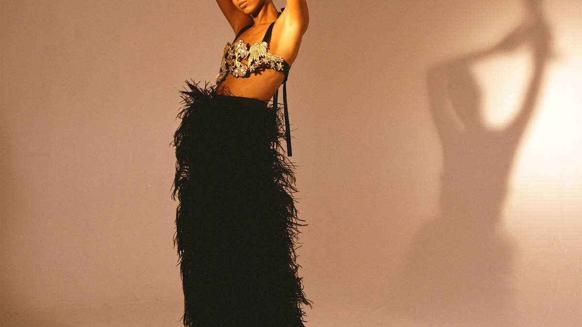 Feature image: model in black feathered skirt and jeweled ornate top
