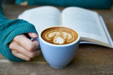 Feature Image: Woman holding mug of coffee reading a book
