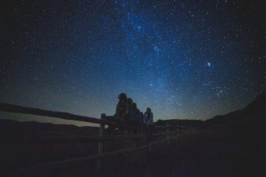 women on a fence stargazing