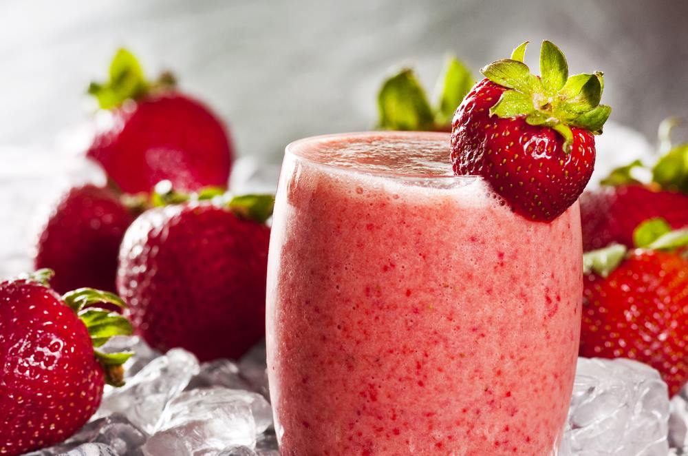 pink strawberry smoothie in glass with strawberry decorations