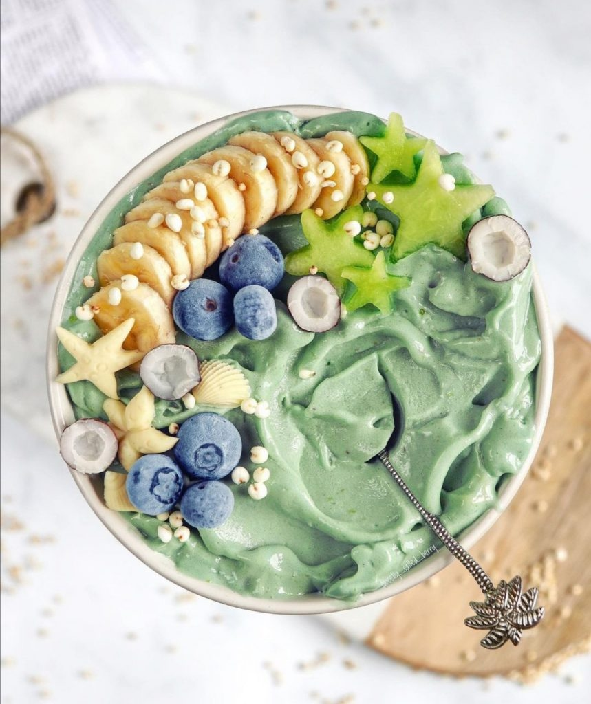 Aqua coloured smoothie bowl with banana and blueberry toppings