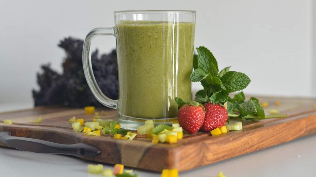 green smoothie in glass jar on wooden board