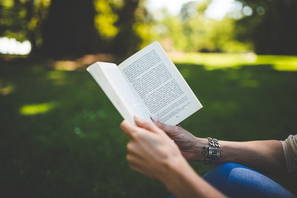 Hands holding a book, reading outside
